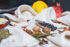 Смешивание различных специй и трав, кашевар и ингридиенты кухни на таблице с оформлением лист и плодоовощ залива Стоковые Фото