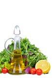 Смешивание салата с бутылкой оливкового масла и лимона изолированных на белизне Стоковая Фотография