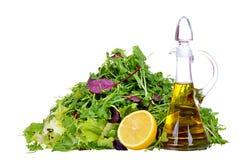 Смешивание салата с бутылкой оливкового масла и лимона изолированных на белизне Стоковое Изображение RF