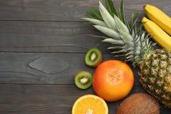 смешивание свежих кокоса, банана, плодоовощ кивиа, апельсина и ананаса на темной деревянной предпосылке Взгляд сверху с космосом  Стоковые Фото