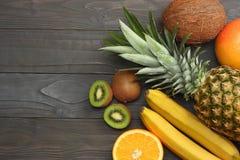 смешивание свежих кокоса, банана, плодоовощ кивиа, апельсина и ананаса на темной деревянной предпосылке Взгляд сверху с космосом  Стоковые Изображения