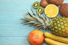смешивание свежих кокоса, банана, плодоовощ кивиа, апельсина и ананаса на голубой деревянной предпосылке Взгляд сверху с космосом Стоковые Изображения RF