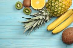 смешивание свежих кокоса, банана, плодоовощ кивиа, апельсина и ананаса на голубой деревянной предпосылке Взгляд сверху с космосом Стоковое Фото