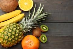 смешивание свежих кокоса, банана, плодоовощ кивиа, апельсина и ананаса на темной деревянной предпосылке Взгляд сверху с космосом  Стоковое Изображение RF