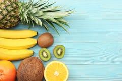 смешивание свежих кокоса, банана, плодоовощ кивиа, апельсина и ананаса на голубой деревянной предпосылке Взгляд сверху с космосом стоковая фотография rf