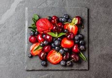 Смешивание ягоды - клубники, вишни, голубика на каменной предпосылке шифера Стоковые Изображения RF