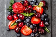 Смешивание ягоды - клубники, вишни, голубика на каменной предпосылке шифера Стоковые Изображения