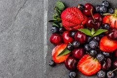 Смешивание ягоды - клубники, вишни, голубика на каменной предпосылке шифера Стоковые Фотографии RF