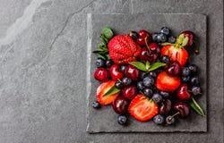 Смешивание ягоды - клубники, вишни, голубика на каменной предпосылке шифера Стоковая Фотография RF