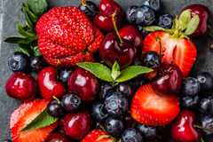 Смешивание ягоды - клубники, вишни, голубика на каменной предпосылке шифера Стоковая Фотография