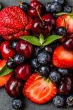 Смешивание ягоды - клубники, вишни, голубика на каменной предпосылке шифера Стоковое Изображение