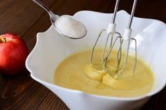 Смешивая бэттер или тесто для яблок-груши испекут или булочка или блинчик Закройте вверх в ингридиентах c деревянного стола Стоковое фото RF