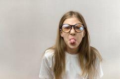 Смешная белокурая девушка в стеклах корчась ее сторона, передразнивающ, имеющ потеху : стоковые изображения rf