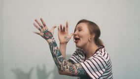 Смешная белокурая девушка в striped задирать рубашки, пальцах встряхивания и разделенном выставкой tounge видеоматериал