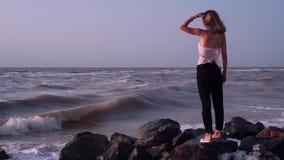 Смешная блондинка в футболке стоит на утесах в море, она получает распыленной от волн видеоматериал