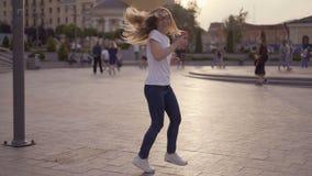 Смешная блондинка имея потеху на улице, танцы девушки и смеясь с телефоном в ее руках 4K акции видеоматериалы