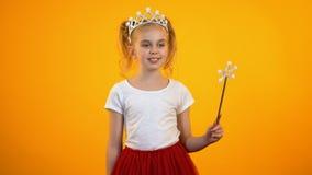 Смешная девушка в обмундировании феи делая движение с волшебной палочкой претендует принцессу видеоматериал