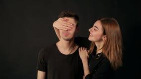 Смешная девушка закрывает глаза рук ` s парня на черной предпосылке акции видеоматериалы