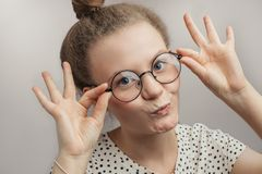 Смешная девушка касаясь ее круглым стеклам стоковая фотография rf