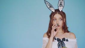 Смешная девушка - кролик с творческими ушами, петрушкой жеваний и взглядами вокруг акции видеоматериалы