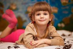 Смешная девушка лежа в кровати Маленькая девочка имеет потеху в кровати стоковое фото