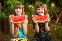 Смешная девушка маленьких сестер ест арбуз в лете стоковые фотографии rf