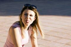 Смешная девушка показывает ее язык и делает стороны стоковые изображения rf