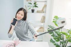 Смешная девушка претендует ее поет песню и использует телефон вместо микрофона Она поет с страстью alric стоковое фото