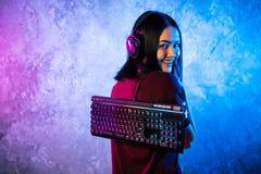 Смешная девушка gamer болвана представляя с клавиатурой игры, играя компютерные игры стоковые фото