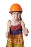 Смешная девушка в красных clenchs защитного шлема ее кулаки Стоковая Фотография