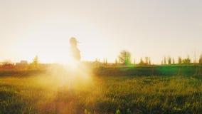 Смешная девушка в розовых стеклах и костюме спорт делает гимнастику Бегущ через зеленый луг на заходе солнца, солнце светит видеоматериал
