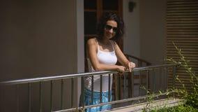 Смешная девушка в стеклах на крылечке вне его гостиничного номера Оно приходит в большое настроение, представляющ для камеры, усм акции видеоматериалы