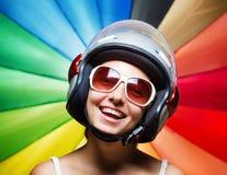 Смешная девушка в шлеме имея потеху. Пестротканая задняя часть Стоковая Фотография