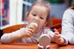 Смешная девушка есть мороженое и смотря в зеркале Стоковое Изображение