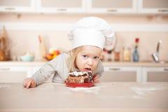 Смешная девушка с шляпой шеф-повара есть торт Стоковое Фото