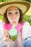 Смешная женщина выпивая зеленый smoothie вытрезвителя на пикнике Портрет стороны близкий поднимающий вверх внешний Стоковые Фото