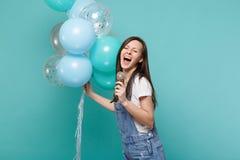 Смешная женщина в одеждах джинсовой ткани с закрытыми глазами поет песню в праздновать микрофона, держа красочные воздушные шары стоковое изображение
