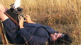 Смешная женщина печатая на винтажной машинке лежа дальше акции видеоматериалы