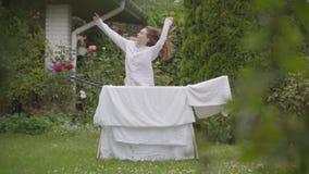Смешная жизнерадостная молодая женщина имеет потеху поя и танцуя на задворк пока делающ работу дома с бельем washday видеоматериал