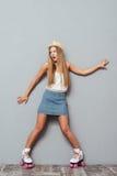 Смешная жизнерадостная девушка в коньках шляпы и ролика имея потеху Стоковые Изображения