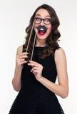Смешная жизнерадостная женщина имея потеху используя стекла и упорки усика стоковые изображения