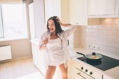 Смешная и шальная девушка кричаща и танцы в кухне Она поет в микрофоне Девушка ждет ее еду, который нужно сделать стоковая фотография