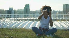 Смешная курчавая с волосами женщина используя шлемофон VR, сидя на лужайке на солнечном дне, устройство акции видеоматериалы