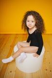 Смешная курчавая улыбка маленькой девочки в студии на оранжевой предпосылке Экземпляр-космос Стоковое Изображение RF