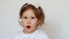 Смешная маленькая девочка есть конфету Счастливый милый ребенок выражает различные эмоции - усмехающся и дразнящ Конец-вверх сток-видео