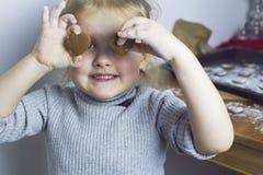 Смешная маленькая девочка играя с печеньями Стоковое Изображение RF