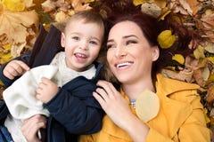 Смешная мать и сын лежа на листьях Стоковое Изображение RF