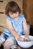 Смешная маленькая девочка варя пирог в кухне, замешивая тесте Стоковые Фото