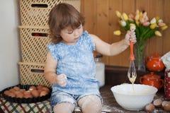 Смешная маленькая девочка варя пирог в кухне, замешивая тесте Стоковые Изображения