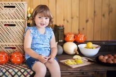 Смешная маленькая девочка варя яблочный пирог в кухне Стоковое Изображение